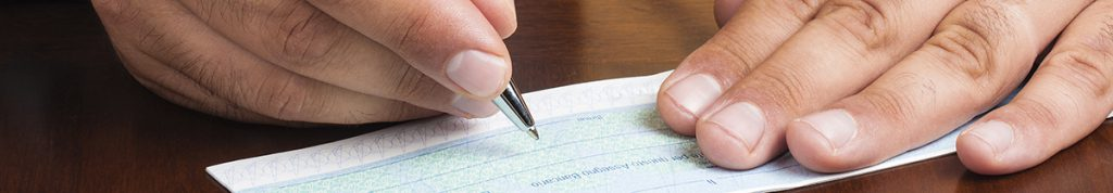 Close up of hands writing a cheque