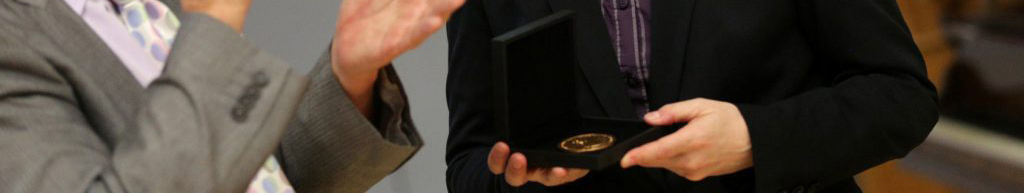 Personal holding gold medal in presentation case whilst another person claps