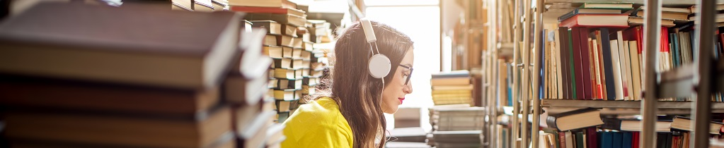 Young woman listening to the music sitting on a heap of books in a library