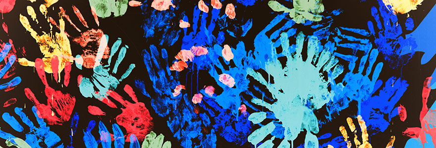 Paint hand prints of many colours on a dark background