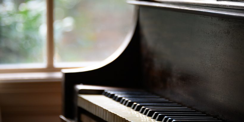 An antique piano sits by a rustic window